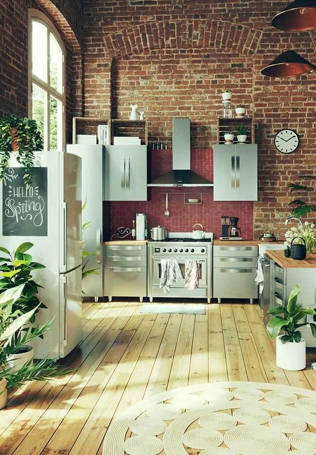 O pé-direito alto e os elementos em inox revelam a tendência industrial dessa cozinha